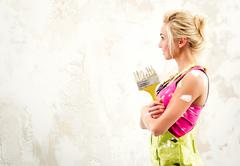 Stock Photo of female in coverall holding paint brush over white obsolete background