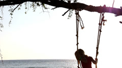 A girl swings on a tree branch overlooking the sea Stock Footage