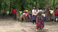 Stock Video Footage of Man showing for Caucasian woman how to hold and shoot with masai bow, Tanzania