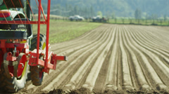 A huge harvesting machine plows through the dirt on a huge field Stock Footage