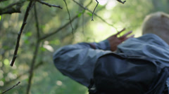 A man moves a branch out of the way while he walks through a forest Stock Footage