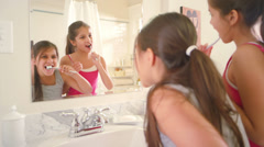 Two cute little sisters brush their teeth together as they get ready for bed - stock footage