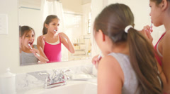 Two sisters share the bathroom as they brush their teeth and get ready for bed - stock footage