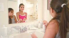 Sisters share the bathroom while they brush their teeth and get ready for bed - stock footage