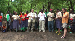 Caucasian man trying to shoot with traditional masai bow, Tanzania Stock Footage