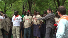 Masai tribe applaud for Caucasian man shooting traditional bow Stock Footage