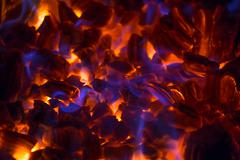 Glowing ember with blue flames - stock photo