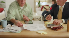 A senior adult gets help with his bills by a professional adviser - stock footage