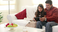 Mom and Dad spend time with their girls while using a tablet computer Stock Footage