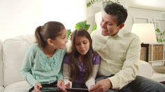 Girls play with their tablets while their father sits with them and watches Stock Footage