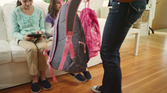 A mother hands her daughters their backpacks before leaving the house for school Stock Footage