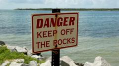 Florida tropical coast beach danger sign rocks 1 Stock Footage