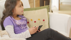 A girl is playing with her tablet computer when her dad comes home from work - stock footage