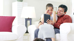 A cute daughter sits on her Dad's lap as they go over a digital tablet together Stock Footage