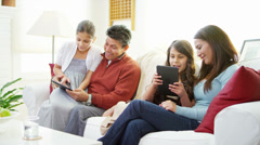 Two parents sit with their daughters and help them use tablet computers - stock footage