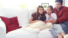 Two cute girls sit with their father and show off their new tablet computer Stock Footage