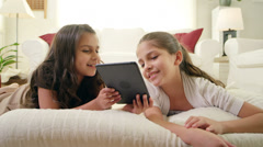 Two kids lay on bed reading tablets Stock Footage