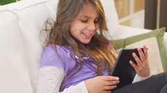 A cute young girl sits on the couch and plays with her tablet computer - stock footage