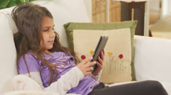 A girl plays with her tablet while waiting for her father to come home from work - stock footage