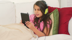 Two girls lie opposite of each other and listen to music on their tablet Stock Footage