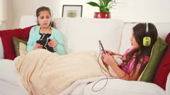 Two girls lie on a couch together and sing along to the music on their tablet Stock Footage