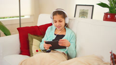 A girl relaxes on a couch and sings along to the music on her tablet computer Stock Footage