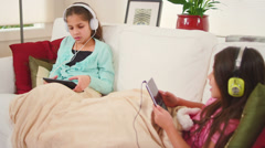 Two sisters sit on a couch and independently sing along to their own music Stock Footage