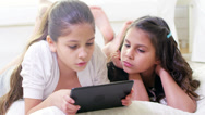 Stock Video Footage of Two girls lie on the ground together in their house and play with a tablet
