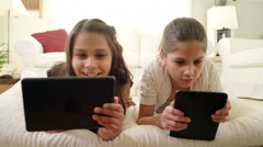 Sisters lie on a pillow together and look at things on their tablets - stock footage