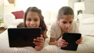 Stock Video Footage of Sisters lie on a pillow together and look at things on their tablets