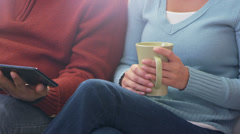 A husband and wife sit on the couch and play with a tablet - stock footage
