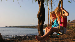 Two adorable little sisters sit on a rope swing together and wave at the camera - stock footage