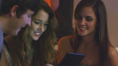A group of friends play with a tablet while hanging out at a house party - stock footage
