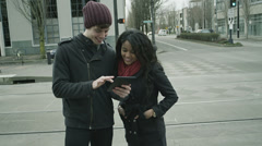 A young couple hangout in the city and play with their tablet computer Stock Footage