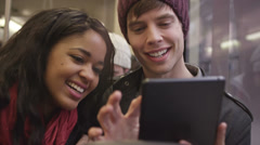 A young couple has a good time on the bus playing with their digital tablet Stock Footage