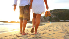 A older couple walk the beach barefoot in Mexico during sunset Stock Footage