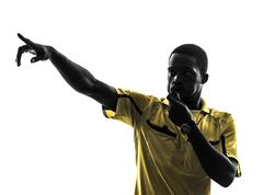 one african man referee whistling pointing  silhouette - stock photo