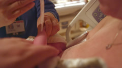 A newborn baby on mommy's lap in the hospital getting a name tag put on Stock Footage