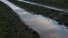 Fast moving clouds reflected in track puddle Stock Footage