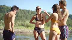 Friends stand in water and talk and laugh - stock footage