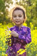 African american girl child in field of yellow flowers Stock Photos