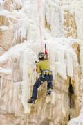Young man climbing the ice using ice axe Stock Photos