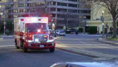 EMS ambulance passes, urban traffic circle, DC - stock footage