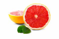 fresh grapefruit with half and leaves isolated on white background - stock photo