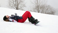 Stock Video Footage of Snowboarder girl lying in the snow