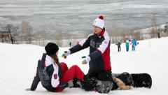 Young man teaches girl to ride a snowboard Stock Footage