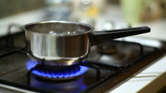 Switching off gas and taking stainless steel pot off gas oven - stock footage