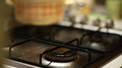 Switching on gas and placing stainless steel pot on gas oven - stock footage