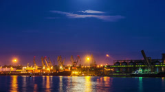 4K. Cranes unload the ship's cargo hold timelapse at dawn Stock Footage