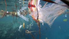Plastic bags and other garbage floating underwater Bunaken Island Stock Footage
